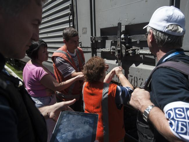 Deal struck ... OSCE mission members observe as a refrigerated train loaded with bodies of MH17 passengers prepares to depart the station in Torez. Picture: Evgeniy Maloletka