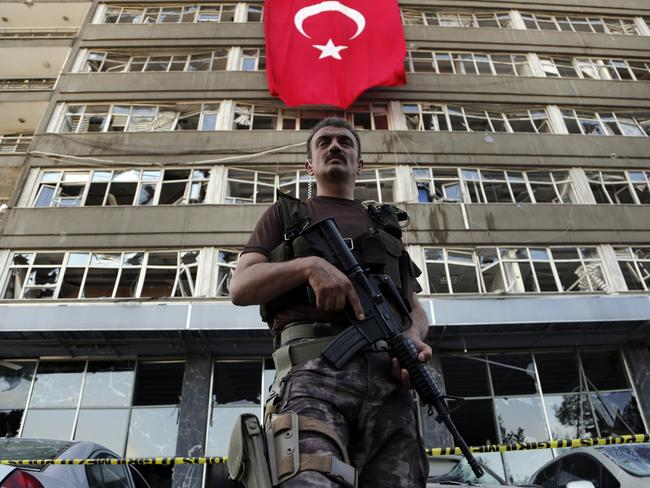 A Turkish special forces officer stands guard in front of a damaged building inside the police base which was attacked by the Turkish warplanes during the failed military coup. Picture: AP/Hussein Malla