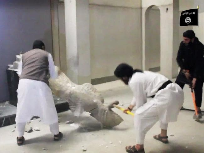 IS militants take sledgehammers to an ancient artefact in the Ninevah Museum in Mosul, Iraq as they destroy a number of shrines and holy sites. AP Photo via militant social media account