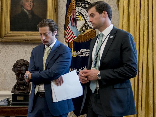 White House aide Johnny McEntee, right, and Treasury Secretary Steve Mnuchin's Chief of Staff Eli Miller, left, stand in the Oval Office. Picture: AP