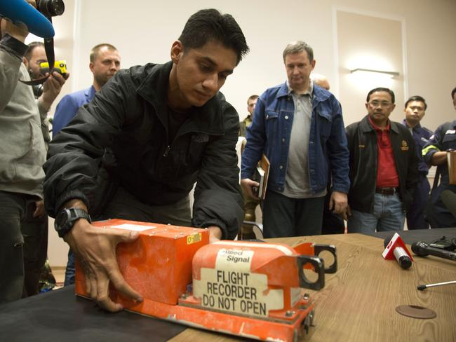 A Malaysian investigator takes a black box from Malaysia Airlines Flight 17 as it is handed over from Donetsk People's Republic officials to Malaysian representatives in the city of Donetsk / Picture: AP