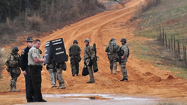 Police are stationed at a check point in Midland City, Alabama, near the home where a school bus shooting suspect is barricaded in a bunker with a young child as hostage.