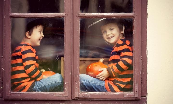 Two cute boys, sitting on a window with pumpkins, smiling