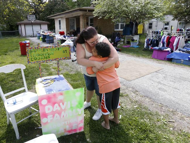 Donnie Davis gives Tristan Jacobson a hug and a kiss outside their home in Springfield, Missouri. Picture: Andrew Jansen/The Springfield News-Leader via AP.