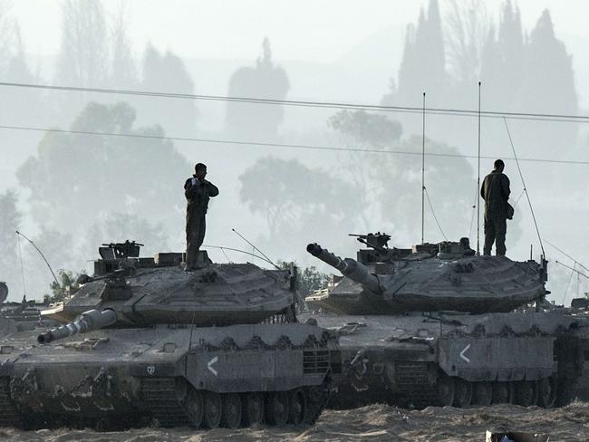 War drums ... Israeli soldiers stand on Merkava tanks in an army deployment area near Israel's border with the Gaza Strip.