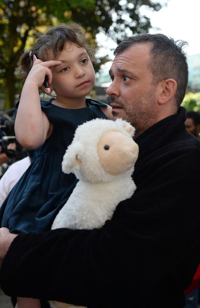 Resident Michael Paramasivan and his daughter Thea Kavanagh, 5, who escaped the inferno. Picture: AP