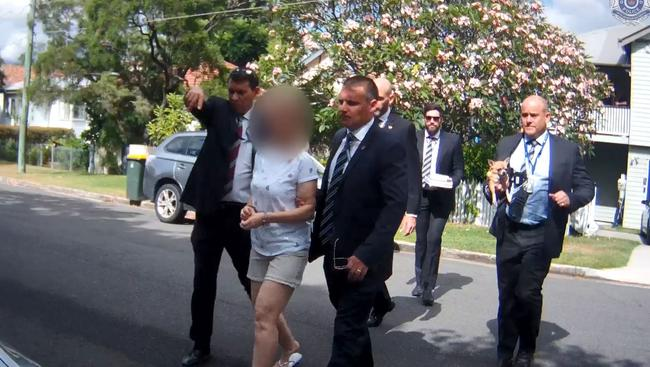 Maree Crabtree is led outside by detectives.