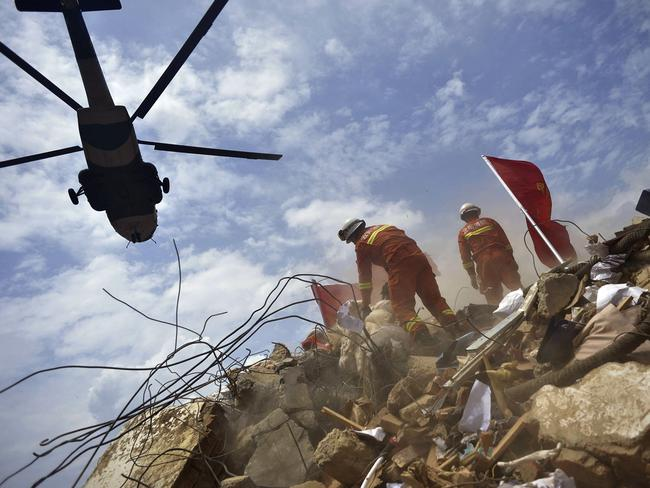 Rubble...A helicopter flies over rescue workers as they search for survivors. Picture: AFP