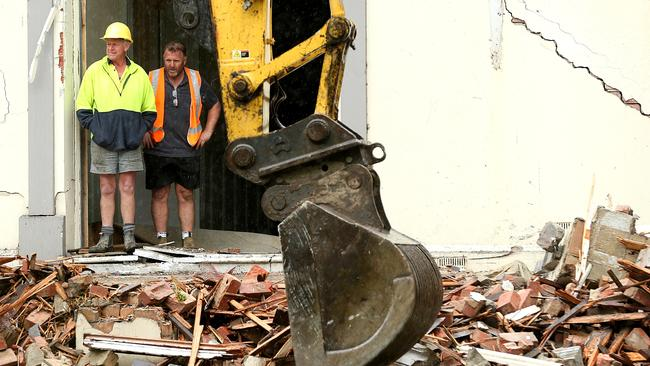 A bulldozer demolishes part of the house. Picture: Mark Stewart