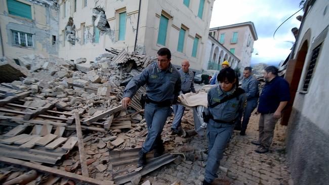 Rescuers carry a man from the rubble after a 6.2 magnitude earthquake struck central Italy. Picture: AFP / Filippo Monteforte.
