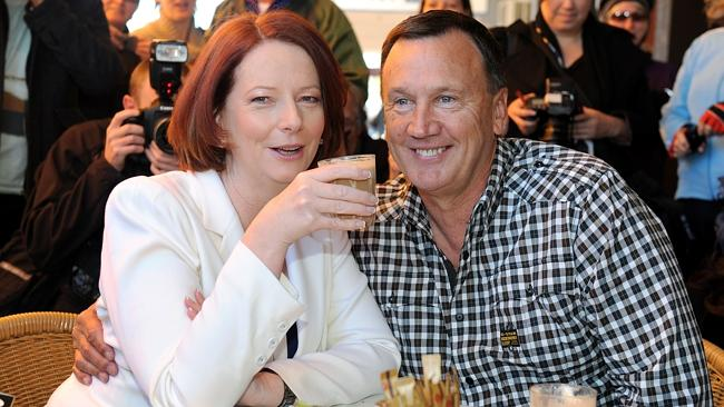 Australian Prime Minister Julia Gillard (L) and her partner Tim Mathieson (R) enjoy their breakfast in front of the media pac...