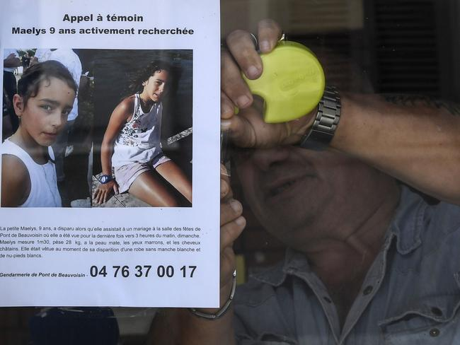 The owner of a bar attaches a missing poster issued by the Gendarmerie of Pont-de-Beauvoisin for Maelys, a 9-year-old girl, who disappeared during a wedding party. Picture: AFP.