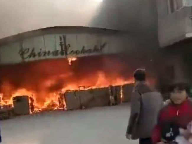 Man emerges from the factory fire engulfed in flames. Picture: Pear Video