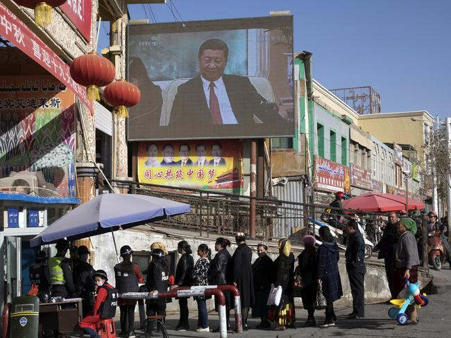 Residents walk through a security checkpoint into the Hotan Bazaar where a screen shows Chinese President Xi Jinping in Hotan in western China's Xinjiang region. Picture: Ng Han Guan