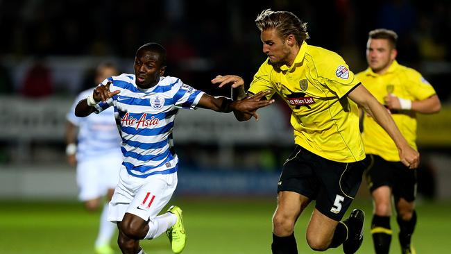 Shaun Wright-Phillips of QPR holds off the challenge of George Taft of Burton.