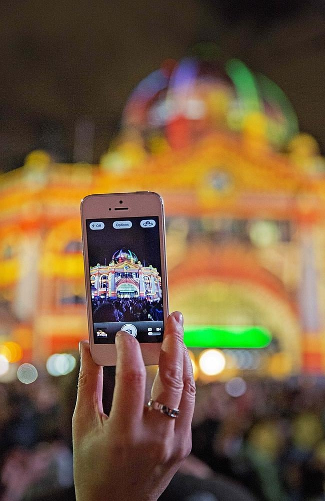 One of the crowd tries to capture White Night at Flinders Street Station on their iPhone.