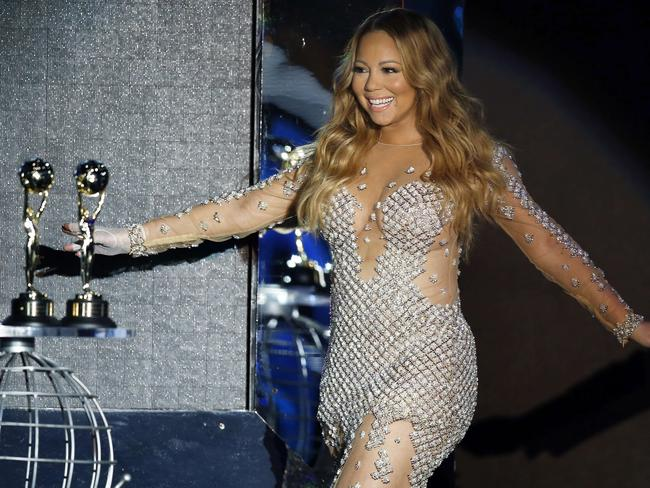 Mariah Carey and two large golden orbs. Also pictured: A couple of award statues. Picture: AFP PHOTO