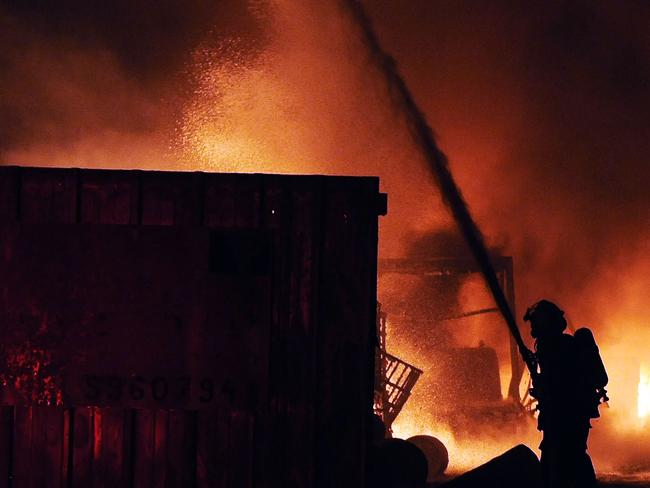 Huge blaze ... Israeli firefighters extinguish a burning factory hit by a rocket fired from the Gaza Strip at an industrial zone in the southern city of Sderot. Picture: David Buimovitch