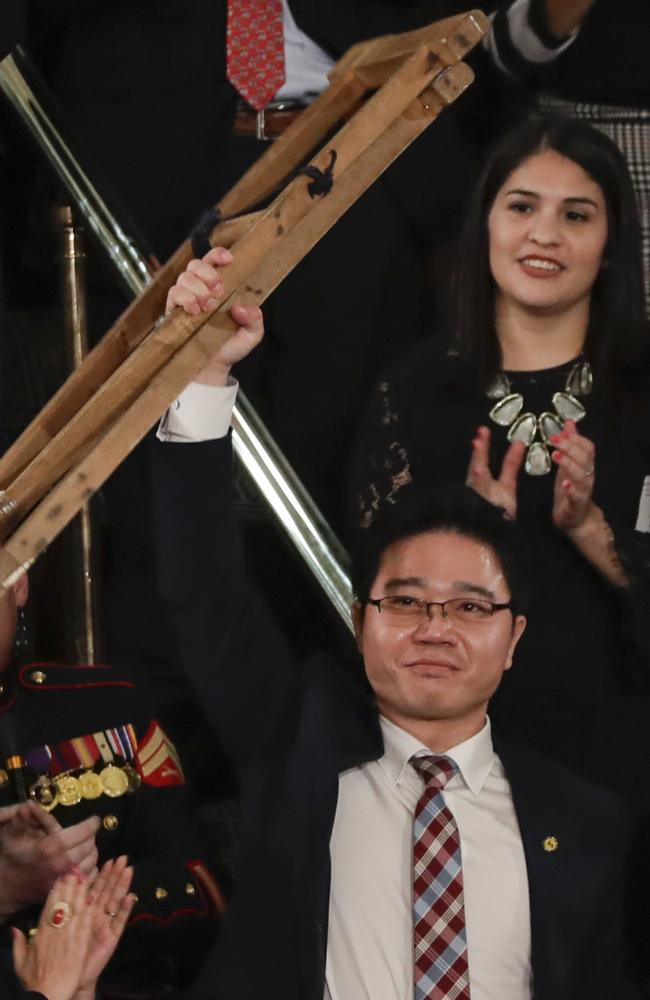 Ji Seong-ho, a North Korean defector, holds up his crutches after his introduction by President Trump this week. Picture: AP/J Scott Applewhite