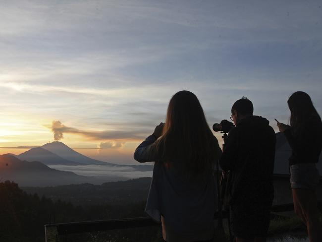 Tourists take photos of the Mount Agung volcano during a sunrise in Kintamani, Bali, in December this year. Picture: Firdia Lisnawati