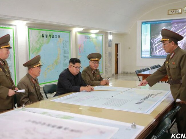 President Kim Jong-un being presented with plans to launch ballistic missiles towards the US territory of Guam. The map in front of him details the flight path of a missile over southern Japan, while the photo on the back wall shows Guam's Andersen Air Force Base. Picture: KCNA