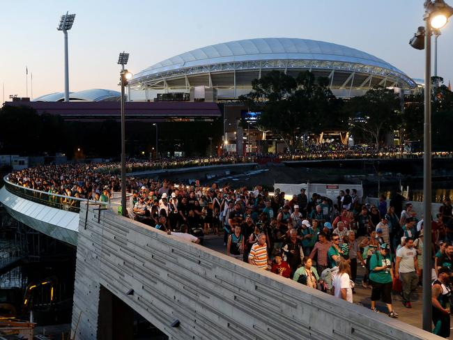 Fans stream across the Torrens footbridge after the first Showdown at the redeveloped Adelaide Oval. Picture: Calum Robertson