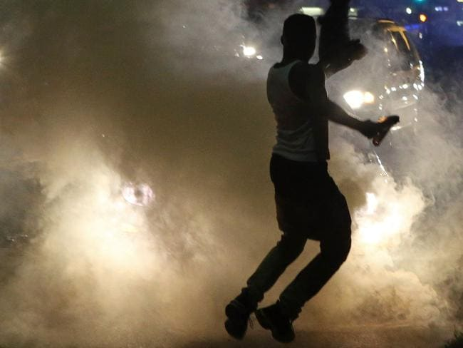Running battles ... Protesters run when the police shoot tear gas in Ferguson on Sunday night. Picture: J.B. Forbes
