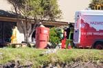 <p>NSW Police and Fire Brigade officers, some wearing protective clothing and breathing apparatus remove evidence from the house in Kelly Street, Bingie. near Batemans Bay. The dwelling is the alleged site of a large drug lab operation.</p>