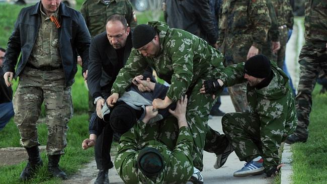 Violent ... Pro-Russian militiamen beat an unidentified man as Russian soldiers stormed a
