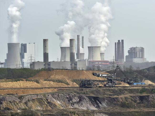 Giant machines dig for brown coal at the open-cast mining Garzweiler in front of a smoking power plant near the city of Grevenbroich in western Germany. Picture: AP Photo/Martin Meissner, File