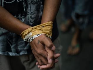 TOPSHOT - A man is seen with his hands bound as male residents are rounded up for verification after police officers conducted a large scale anti-drug raid at a slum community in Manila on July 20, 2017. One resident was killed in the raid according to police. President Rodrigo Duterte swept to an election victory last year largely on a pledge to wipe out his nation's illegal drugs trade within three to six months, saying he would do so by killing thousands of people. Duterte fulfilled his vow on the death toll, drawing condemnation from rights groups who warned he may be orchestrating a crime against humanity as police and unknown assassins filled slums with bullet-ridden corpses. / AFP PHOTO / NOEL CELIS