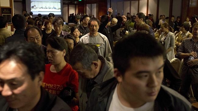 Angry ... Relatives of Chinese passengers on-board the missing Malaysia Airlines 370 walk out from a video-conference with Malaysian officials in protest at the difficulties of communications in Beijing.