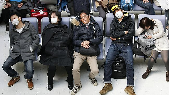 Travellers stranded at Narita International Airport snooze. Picture: AP