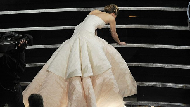 Jennifer Lawrence stumbles as she walks on stage to accept the best actress Oscar for Silver Linings Playbook. Picture: AP