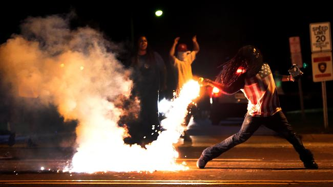Defining image ... a demonstrator throws a tear gas container back at police on Chambers Road and West Florissant. Picture: AP Photo/St Louis Post-Dispatch, Robert Cohen