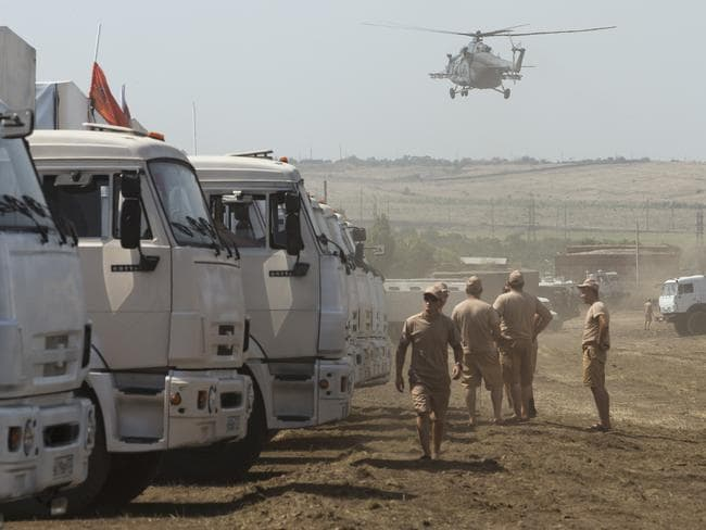 Days of controversy ... a Russian military helicopter prepares to land near a convoy of white trucks with humanitarian aid parked in a field about 28 kilometres from the Ukraine border. Picture: Pavel Golovkin