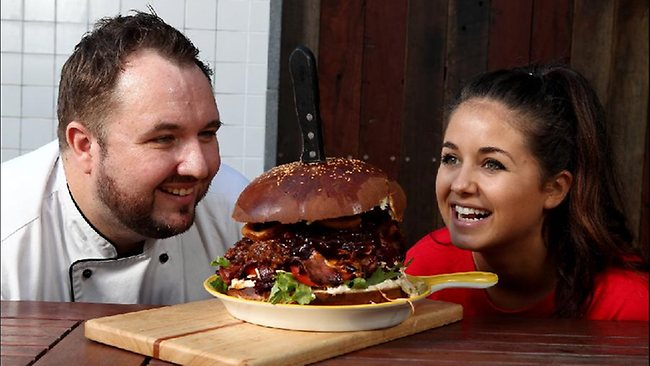 A 1.6kg, 9000kj Phat Bastard Burger challenge is underway at Surfers Paradise.