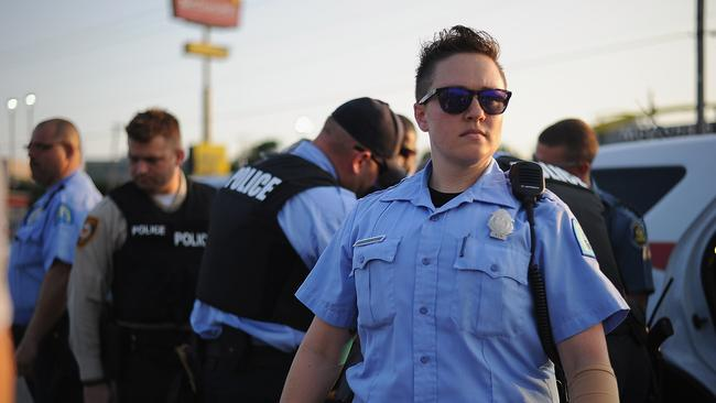 Out in force ... police officers monitor the peaceful protest on West Florissant Avenue in Ferguson. Picture: AFP/ Michael B. Thomas