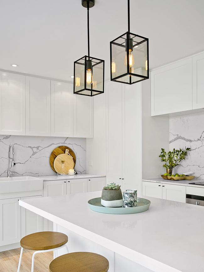 Marble splashbacks and modern lighting in the Beecroft home's kitchen.
