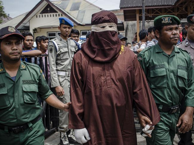 An executor known as 'algojo' stands as prepare public caning for violations against sharia law on March 20, 2017 in Banda Aceh, Indonesia. Picture: Ulet Ifansasti
