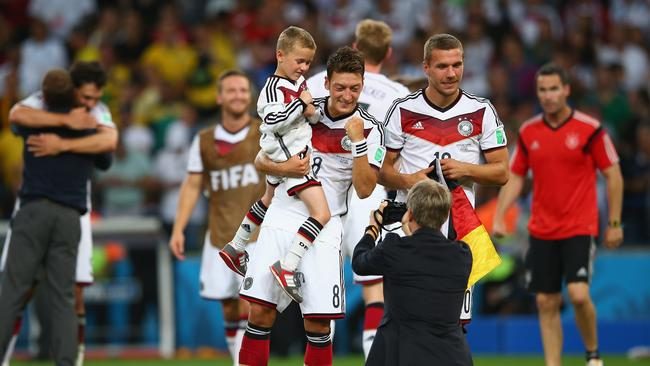 Mesut Oezil of Germany (C) celebrates with Lukas Podolski (R) and his son Louis Podolski.