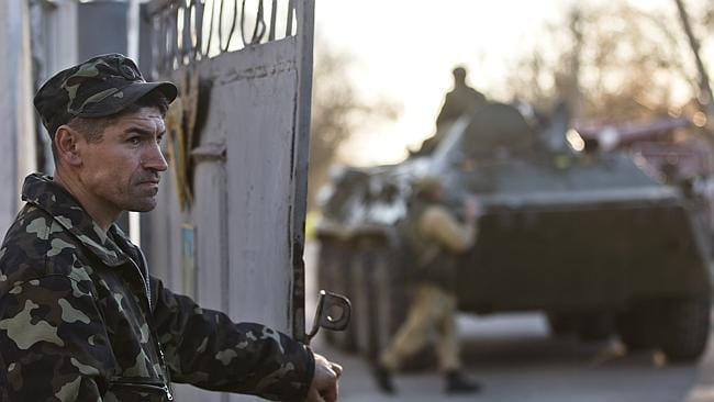 An Ukrainian serviceman opens a gate ... back dropped by an armored personnel carrier bel