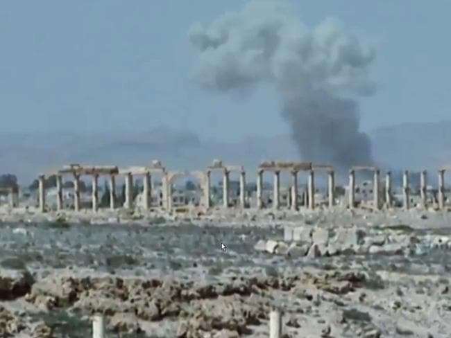 Devastation ... smoke rises over the ancient ruins of Palmyra as the Islamic State takes full control of the city after violent clashes with pro-government forces. Picture: Supplied