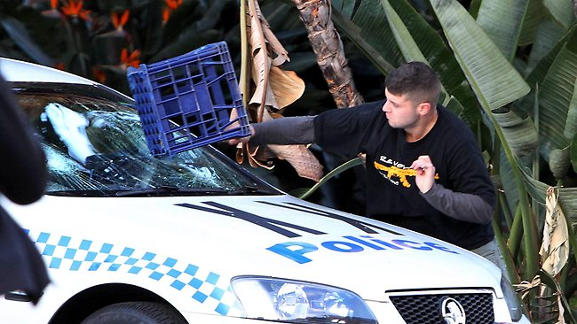 A rioter smashes a police window with a milk crate in the Islamic riots in the CBD of Sydney. Picture: Jane Dempster