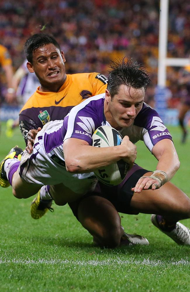 Cooper Cronk of the Storm dives to score a try while tackled by Ben Barba.
