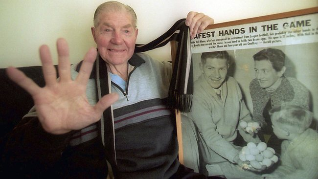 Former Collingwood captain and coach Neil Mann in 2002 with a photo of an article featuring him that featured in the Herald. Picture: Peter Ward