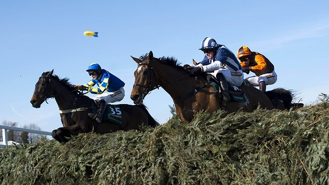 Winner Auroras Encore ridden by Ryan Mania (L) and Teaforthree ridden by Nick Scholfield (front) jump the last fence in the Grand National at Aintree. Picture: Adrian Dennis