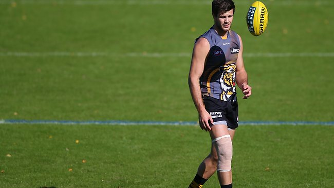 Trent Cotchin walks with the bandage on his left leg during Richmond training.