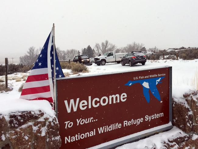 An sign of the National Wildlife Refuge System is seen at an entry of the wildlife refuge. It has since been covered over with an American flag. (Les Zaitz/The Oregonian via AP)