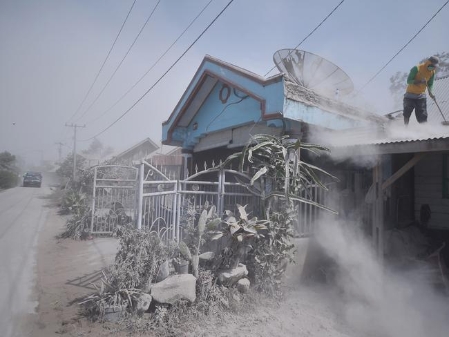 A man cleans dust from a roof of a house in Karo, North Sumatra. Picture: Lana Priatna / AFP
